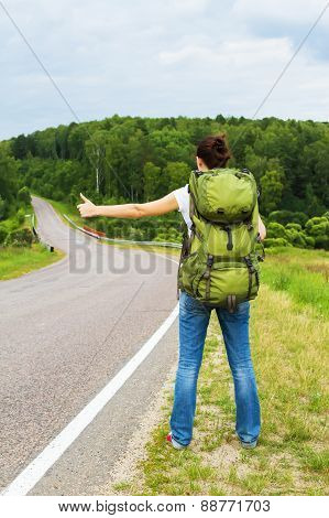 Woman with backpack hitchhiking on a country road poster