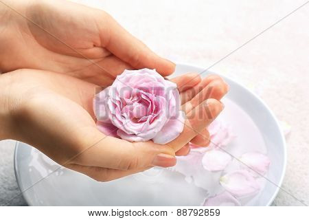 Female hands with bowl of aroma spa water on table, closeup