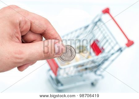 Male hand throws a coin into money box of the shape of trolley.