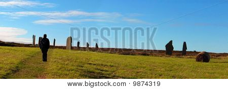 Backpaker walking forward the Ring of Brodgar (or Brogar). It is a Neolithic henge and stone circle in Orkney, Scotland. a magnificent ring almost 104m in diameter poster
