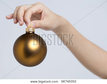 Christmas ball holding by fingers