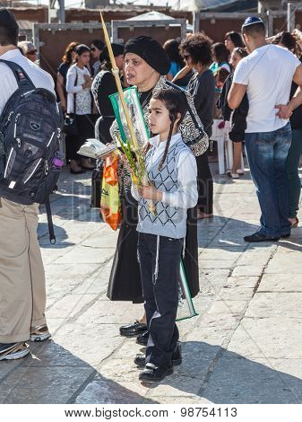 JERUSALEM, ISRAEL - OCTOBER 12, 2014: The area in front of Western Wall of Temple filled with people. Morning autumn Sukkot. Many believers have brought prayer books and four ritual plants