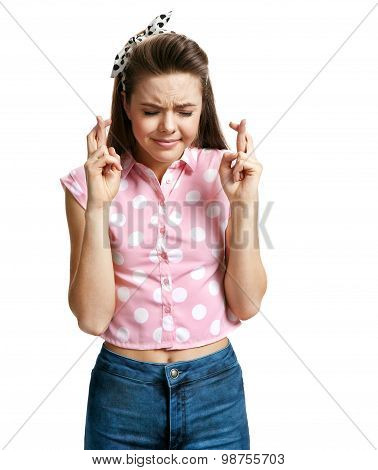 Girl Keeping Fingers Crossed And Eyes Closed While Making A Wish
