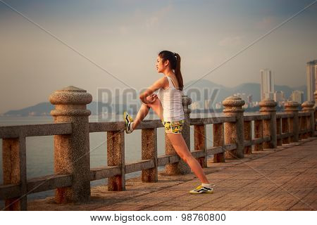 asian brunette girl in sports-shirt and shorts does morning exercises on embankment against sea at dawn poster