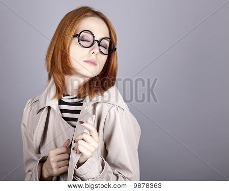 Young red-haired girl in glasses and cloak. Studio shot. poster