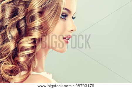 Smiling Beautiful girl light brown hair with an elegant hairstyle , hair wave ,curly