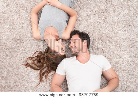 Pleasant couple lying on the carpet