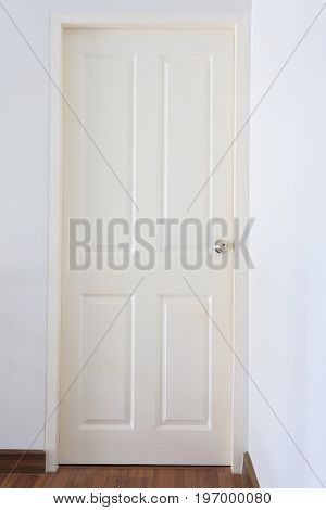 White Wood Pane Door Closed And Silver Knob Lock In Industrial Building House
