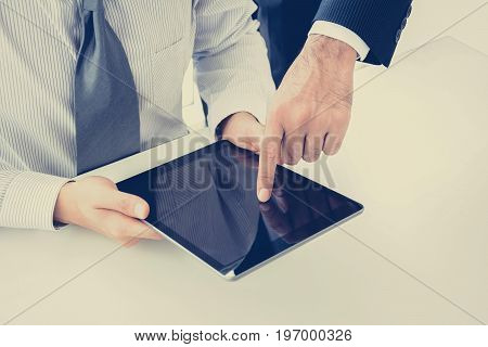 Two businessmen using tablet computer with one hand touching the screen business discussion concept - vintage style colors with focus on finger at screen