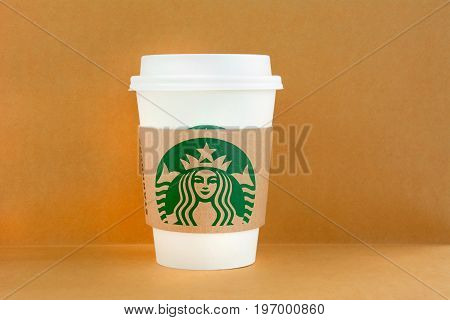 Bangkok Thailand - Mar 04 2015 : Starbucks take away coffee cup with logo on sleeve Starbucks brand is one of the most world famous coffeehouse chains from USA.