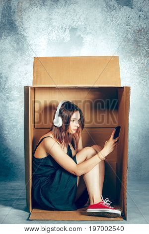 Introvert concept. Woman sitting inside box and working with mobile phone