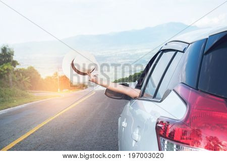 Relaxed happy traveler Young beatiful asian gilr holding white Hat weave and Reach out of the car at sunset and beautiful view with mountain road background.