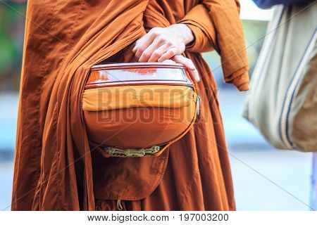Thai monk with alms to a Buddhist monk on morning.