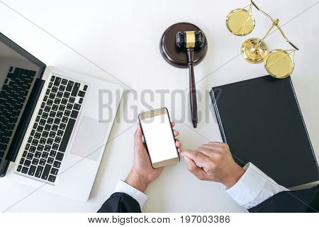 Male lawyer or judge working with smart phone and scales of justice Law book gavel report the case on table in modern office Law and justice concept. Top view.