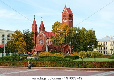 MINSK BELARUS - OCTOBER 1 2016: Unknown people are on Independence Square near known Catholic church of St. Simeon and St. Helena (Red Church) Minsk Belarus