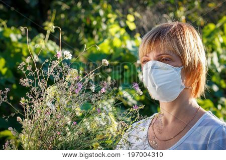 Woman In Protection Mask Holding Bouquet Of Wildflowers And Trying To Fight Allergies
