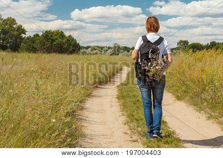 Hiker With Backpack Walking On Rural Road