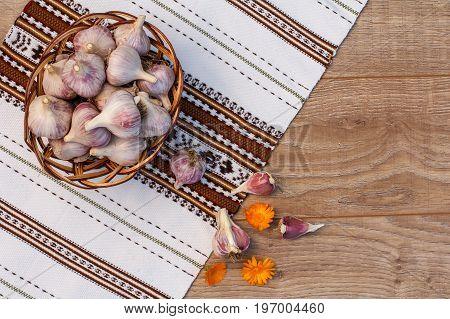 Ripe Garlic In A Wicker Basket On Wooden Board