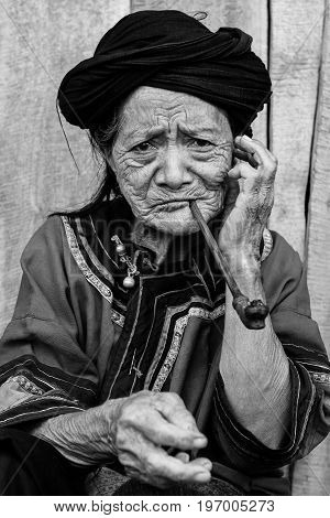 2010-07-25 in Phongsali, Laos: portrait of old hill tribe woman in traditional clothes smoking a pipe