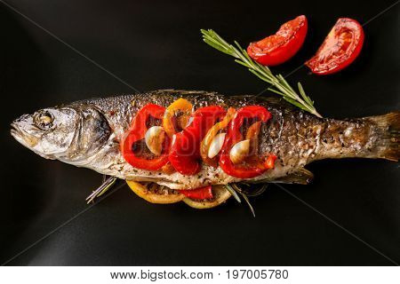 Plate with baked sea bass fish and vegetables, closeup