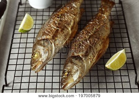 Two baked sea bass fish with lime on grid
