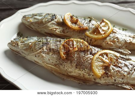 Delicious baked sea bass fish on white plate