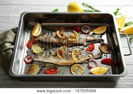 Baking pan with sea bass fish and garnish on wooden background