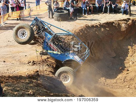 Blue Car Ramping Out Of Steep Dugout