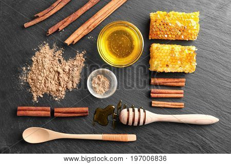 Wooden flatware, cinnamon, bowls with honey and powder on table