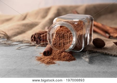 Glass jar with powdered cinnamon and sticks on light table
