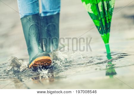 Girl In Rubber Boots Outdoors In Rainy Day