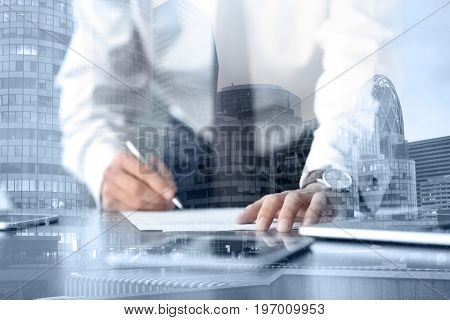 Concept of consulting. Double exposure of cityscape and businessman signing documents at table