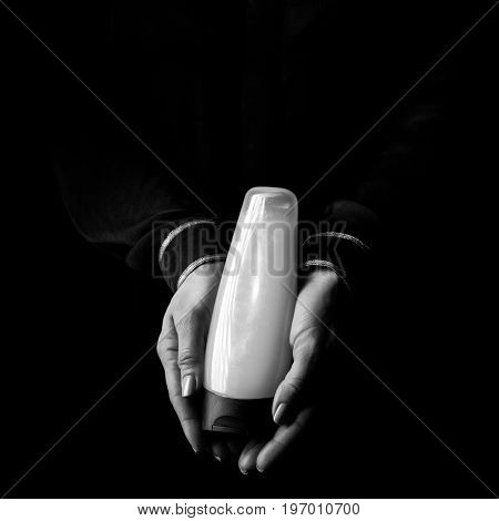 Female Hands Isolated On Black Showing Bottle Of Cosmetics