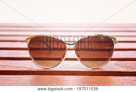 Modern sunglasses on wooden surface. Summer vacation concept