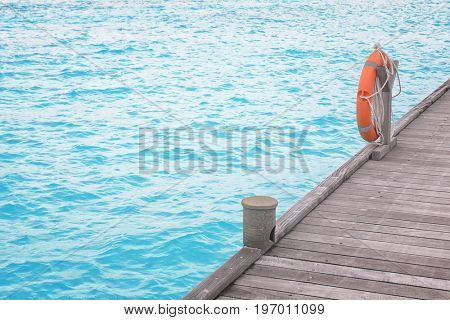 Wooden pontoon with flotation ring at sea resort in summer day