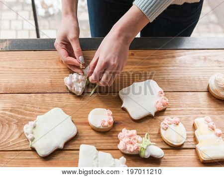 Girl embellishing wedding gingerbread with ribbon. Tasty food, sweet dessert top view. Beautiful present on wooden background, baking concept