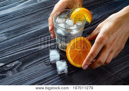 Preparation of a refreshing beverage with ice and citrus fruits on a dark wooden table. Bartender's hands at work close-up. Design of the drink before serving