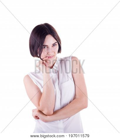 A portrait of beautiful and awkward young lady isolated on a white background. A lonely and unsure brunette woman in a stylish white blouse. Human face expressions concept.