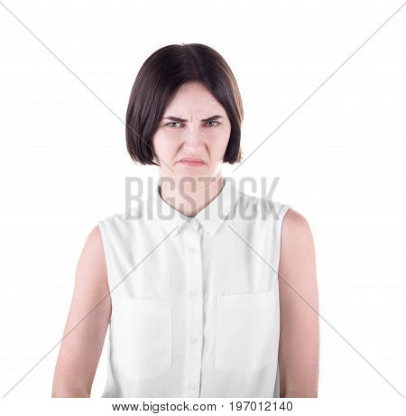 A disappointed business lady isolated over the white background. An expressive and judging girl with a short black haircut. A stressed young woman wearing a white casual blouse.