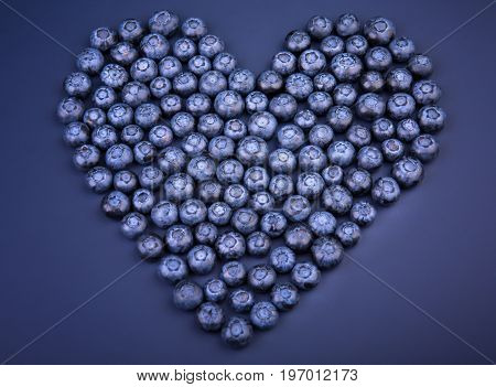 A top view of a group juicy blueberries organized in a shape of a heart on a saturated blue background. Sweet blueberries for healthful summer breakfasts. Beautiful vegan berries in a heart shape.