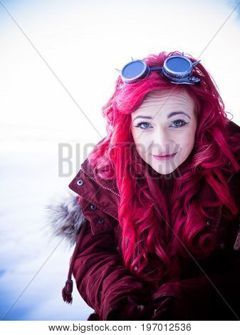 The red-haired woman is standing in coat in winter forest