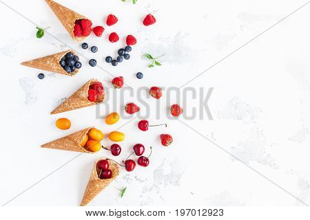 Fruit background. Fresh fruit and berries in waffle cones. Summer concept. Flat lay top view copy space