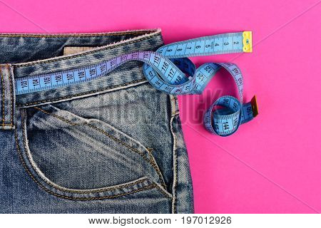 Denim Trousers And Measure Tape Isolated On Pink Background