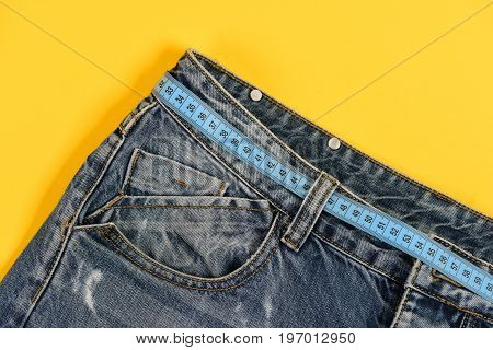Close up of jeans belt loops and pocket. Healthy lifestyle and dieting concept. Top part of denim trousers isolated on yellow background. Jeans with blue measure tape instead of belt.