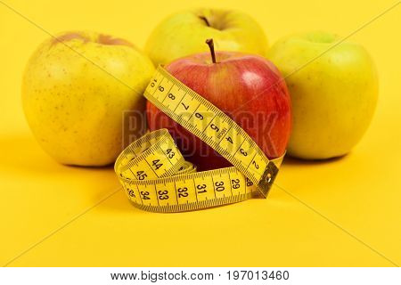 Apples Of Red And Yellow Colour Wrapped With Measuring Tape