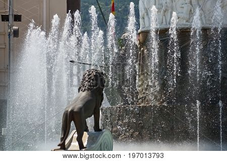 Sculpture of a lion and water fountain under the monument of Alexander the Great