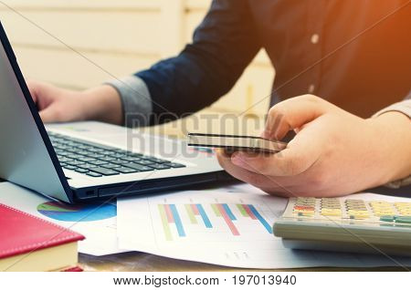 young business man using smartphone laptop with data sheet calculator on desk analyzing and calculate savings finances economy concept sunlight effect soft focus selective focus vintage tone