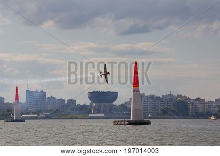 Kazan, Russia - July 22, 2017: Red Bull Air Race - race airplane flies in front of Kazan Family center, telephoto