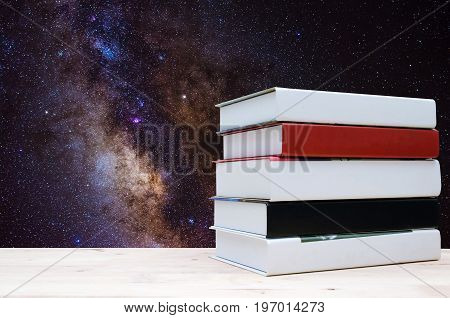 stack book on desk no labels blank spine with milky way galaxy background long exposure photograph with grain or noise and soft focus. color tone effect education back to school concept
