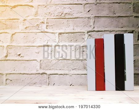 stack book on desk no labels blank spine with brick wall background selective focus copy space sunlight effect education back to school and business concept color tone effect
